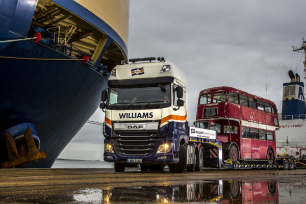 Williams Shipping truck transporting an old red london double decker
