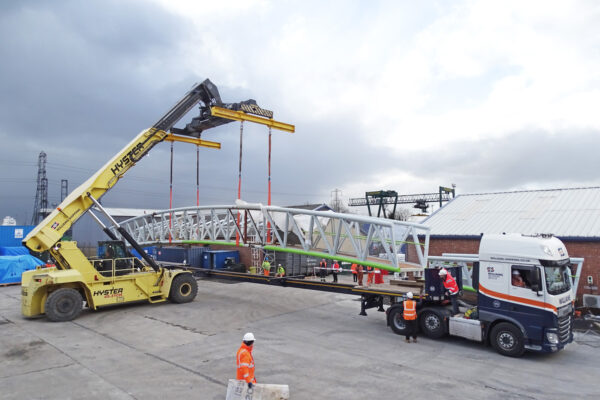 Hyster Reach Stacker lifting a bridge onto the back of a Williams Shipping truck
