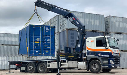 A shipping container being lifted by a hiab crane truck