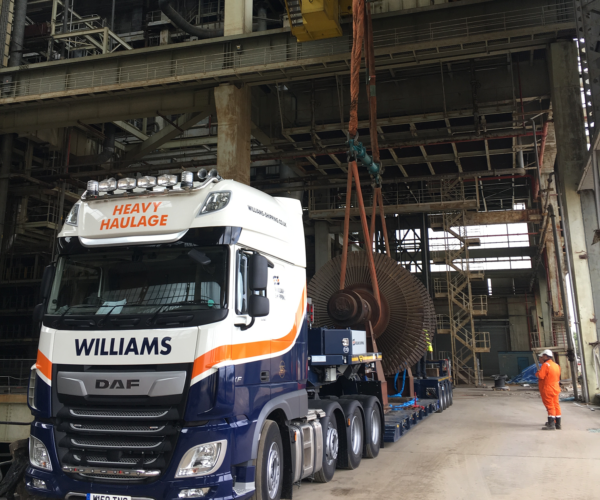 Mechanical equipment being loaded onto a low loader trailer