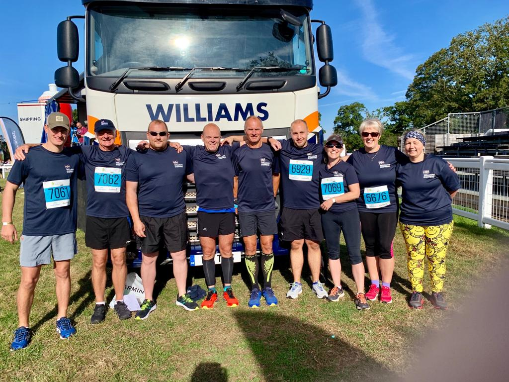 The Williams Shipping New Forest Marathon team in front of a Williams Shipping lorry